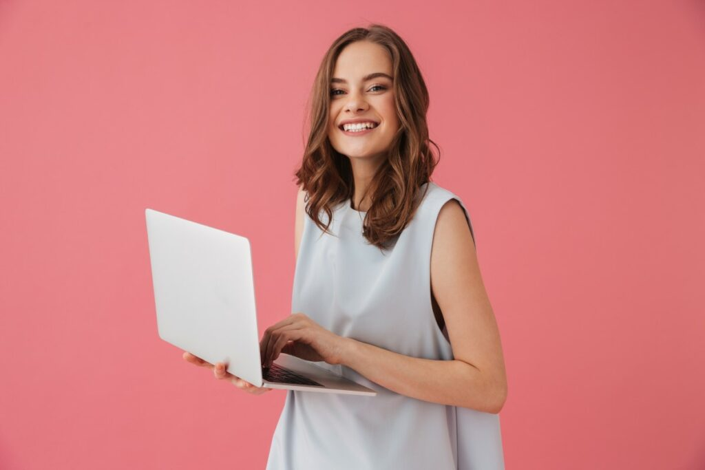 Woman smiling with laptop in her hand reading about how to find a job you love