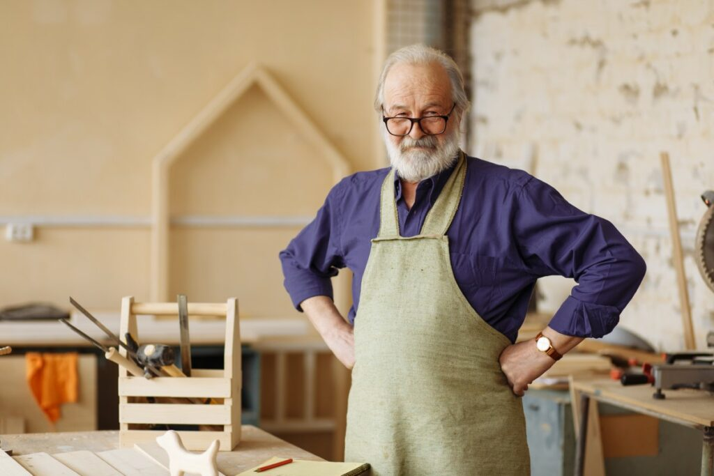 elderly man with glasses wearing a purple button down and and a beige apron, stemming his hands into his hips