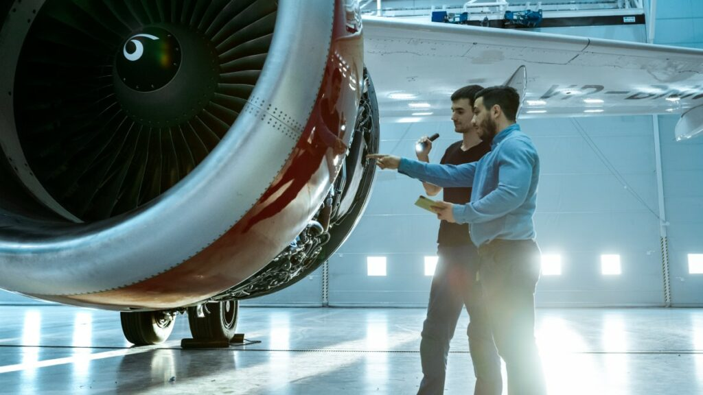 Two men standing in front of the turbine of an airplane