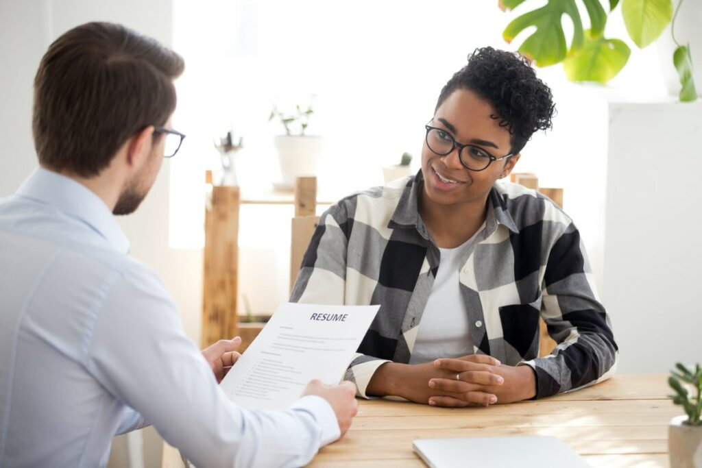 young person that applied for a job having a job interview smiling at the interviewer holding their resume