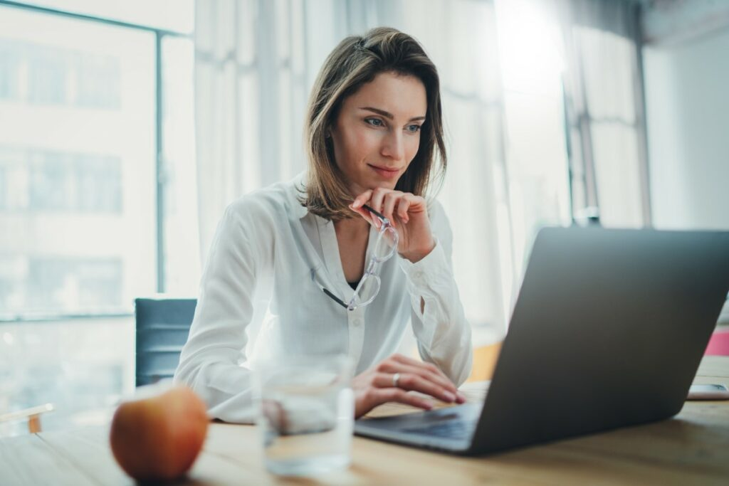 Woman sitting at a desk in front of a laptpo reading about the highest paid bachelor degree jobs