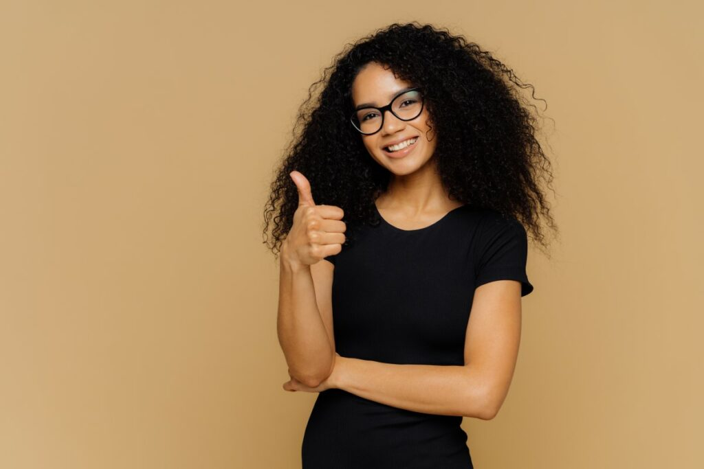 Woman dressed in black with glasses smiling and showing a thumbs up in front of a beige background