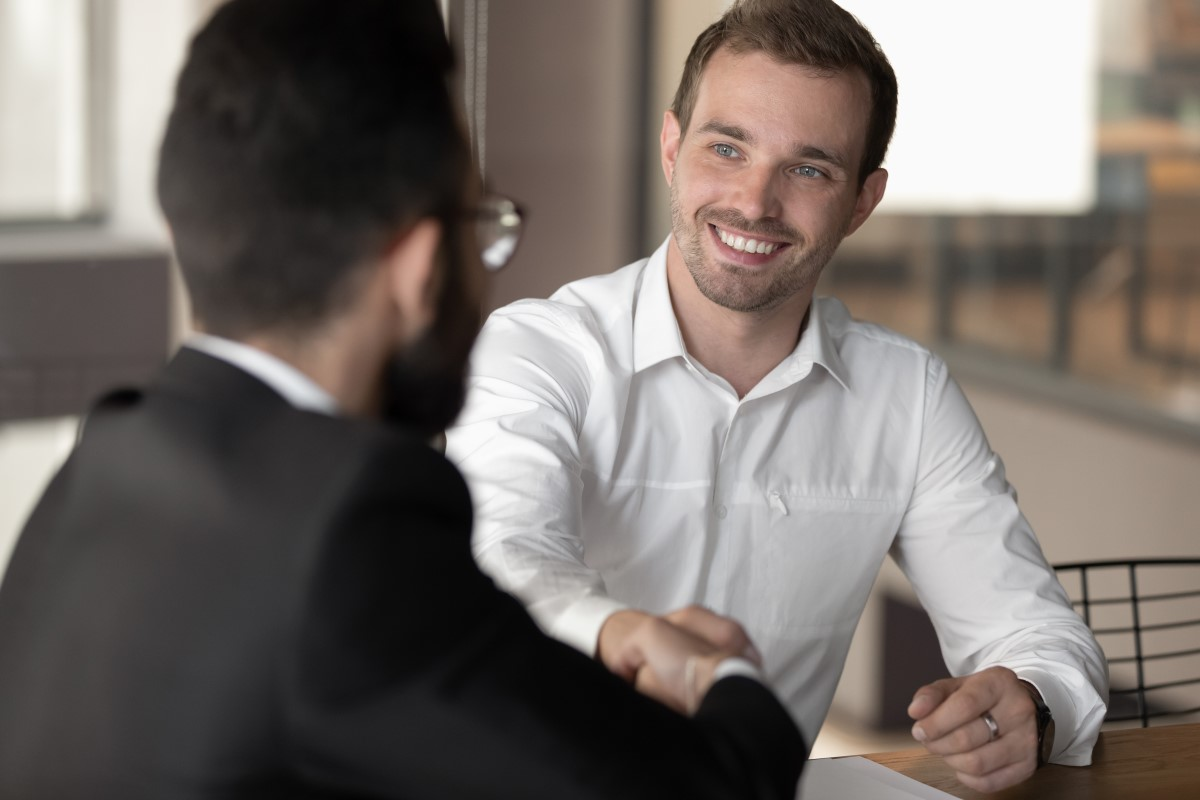 Two men shaking hands sitting at a table, wearing a white button-down, confidence appearance, smiling confidently while mastering his body language during a job interview