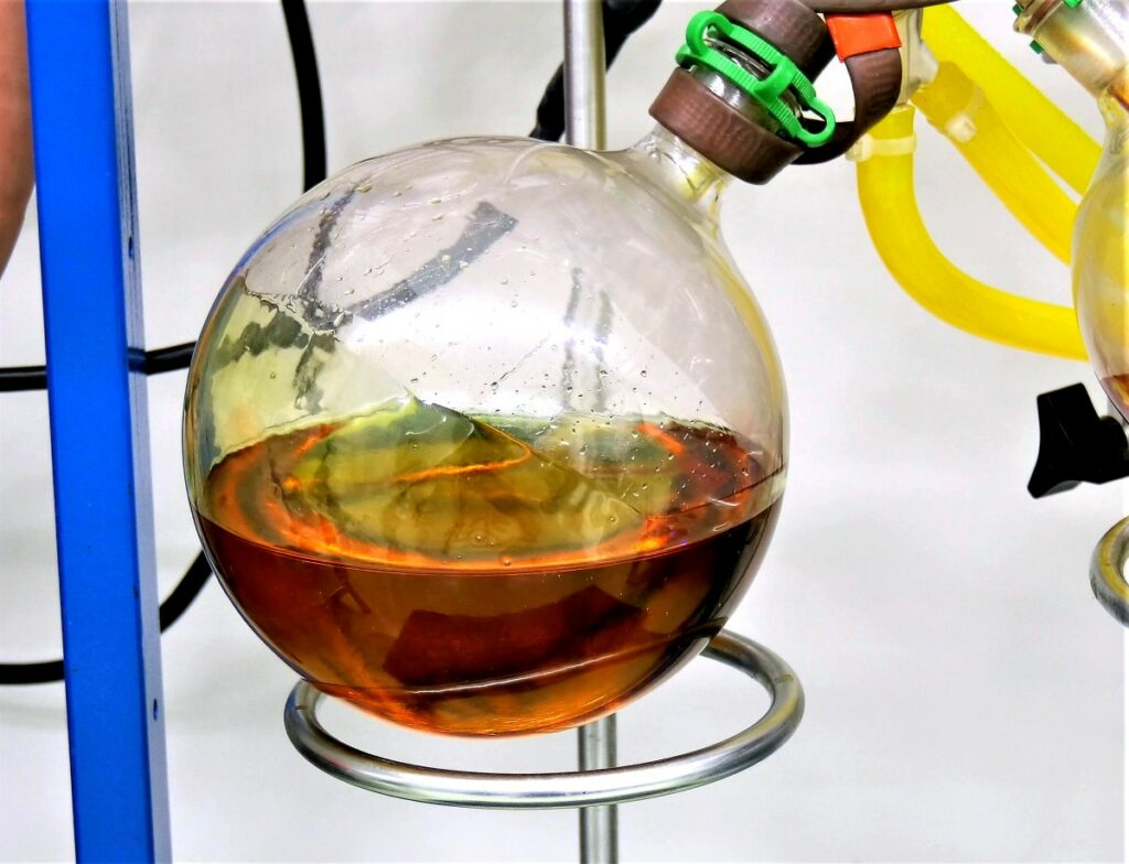 bulbous Erlenmeyer flask filled with a brown liquid, sealed with a brown cup