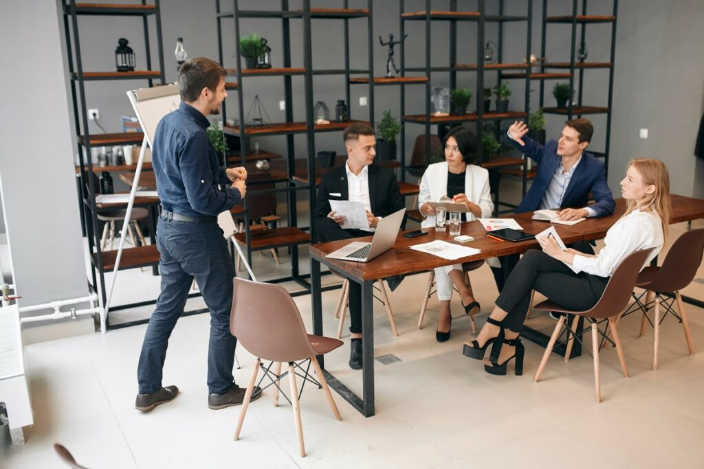 five people in a modern cafe like office space, 4 sitting at a table, one standing in front of them on a flipchart