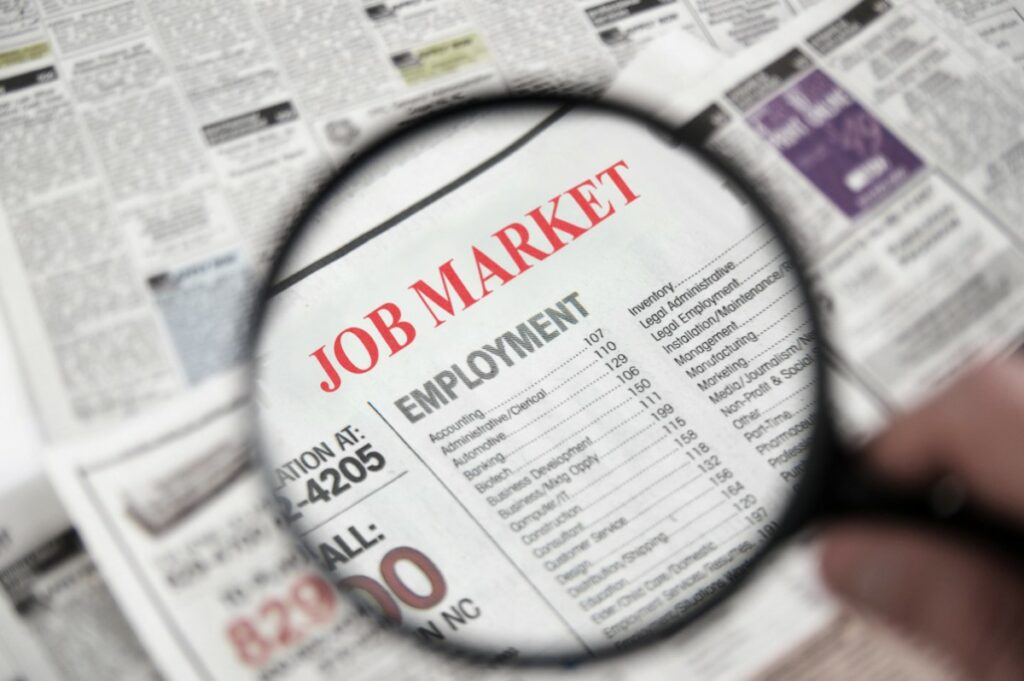 Newspaper with a magnifying glass above the job market and employment section in order to find a job