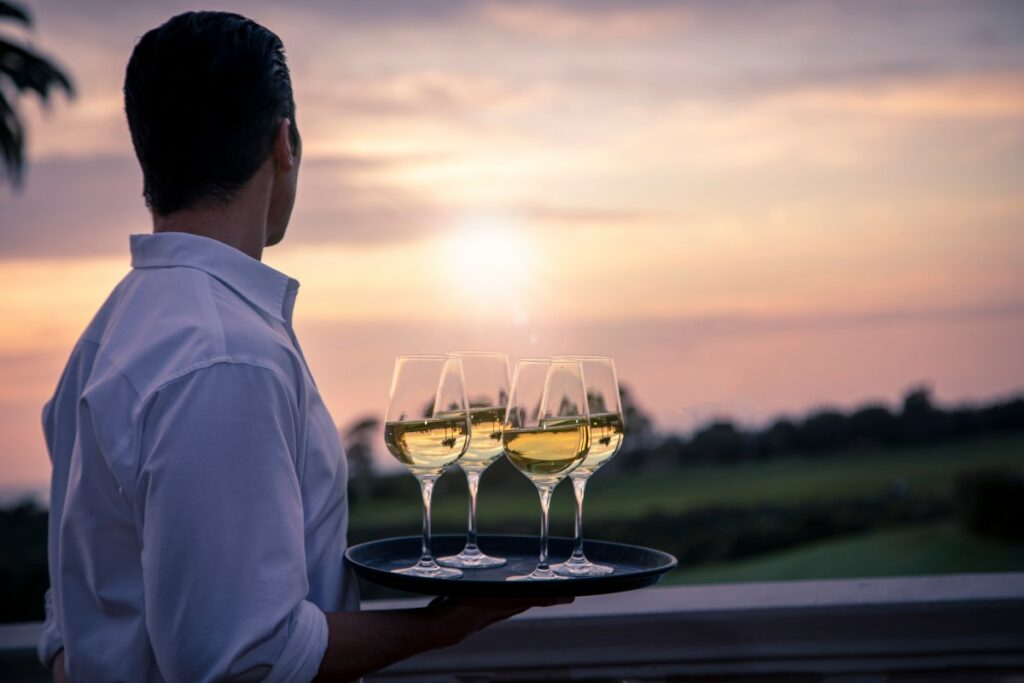 man in a white button down holding a trey with wine glasses filled with white wine looking into the sunset