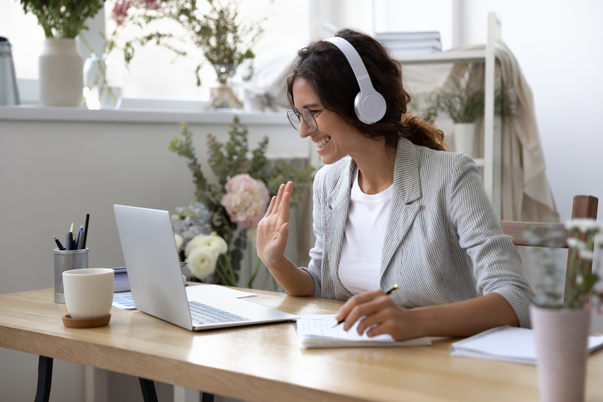 woman with a light grey blazer wearing glasses and white headphones sitting on a desk waving in front of her laptop