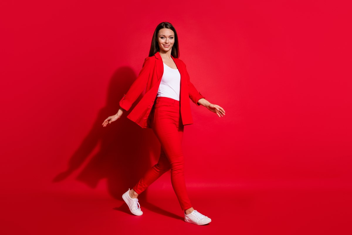 woman dressed in a red pantsuit, white shirt and white sneakers walking in front of a red background