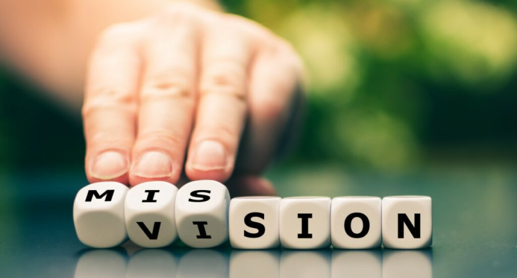 White dice with black letters are turned over, from the word mission the word vision is created