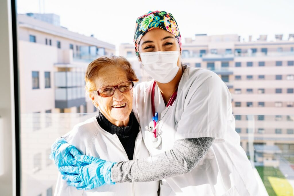 nurse with mask and blue gloves hugging an elderly woman, both are smiling