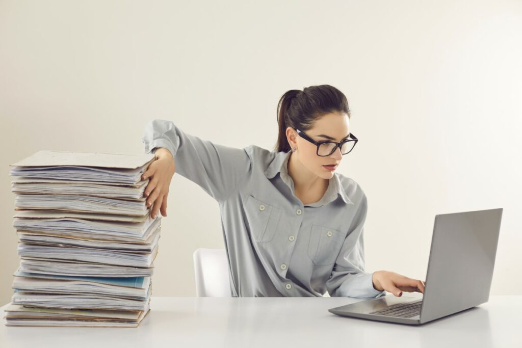 woman with grey blouse and black glasses typing on a laptop with one hand, holding back a pile of paper work with her other hand