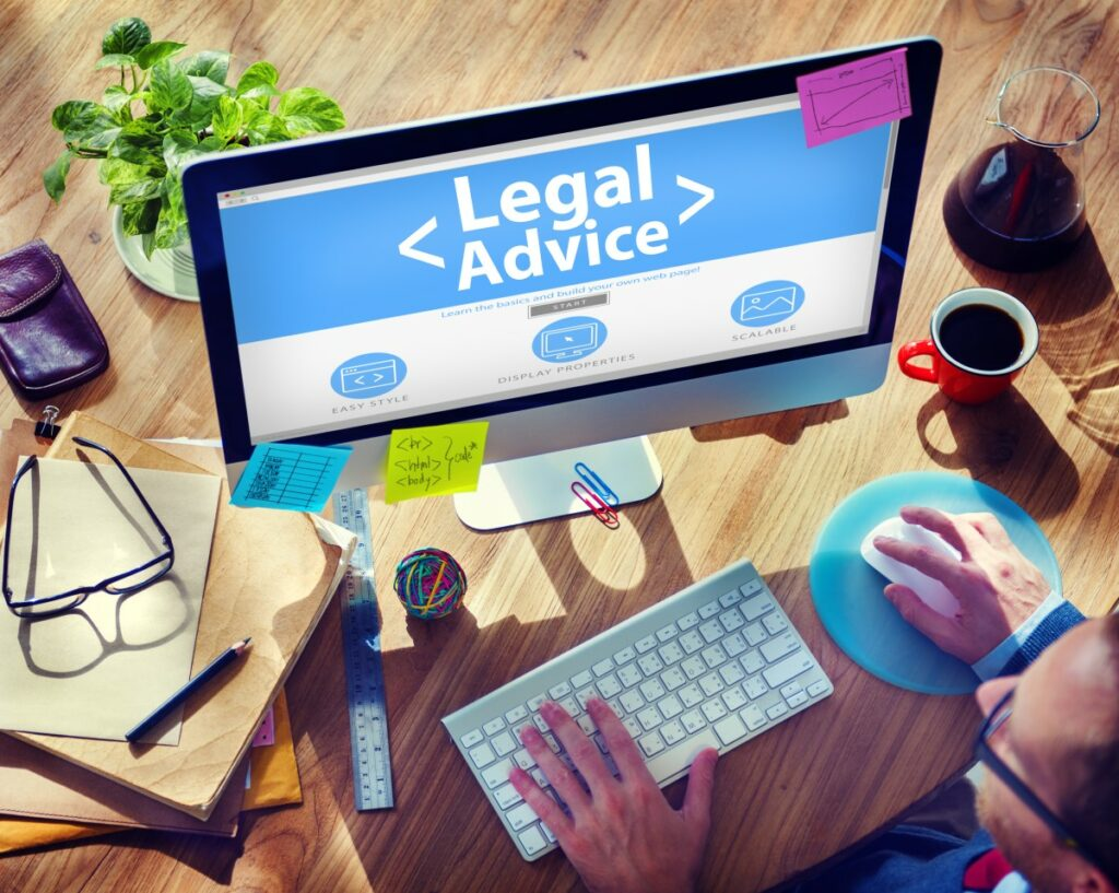 text <legal advice> shown on a srcreen on a desk with pen, ruler, keyboard, mouse, coffee etc.