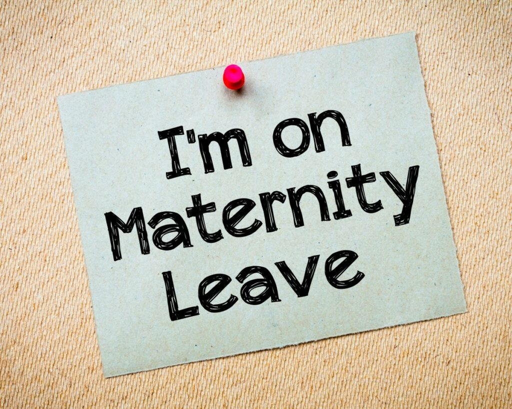 blue paper with big black letters spelling out I'm on Maternity Leave on a pinboard with red pin