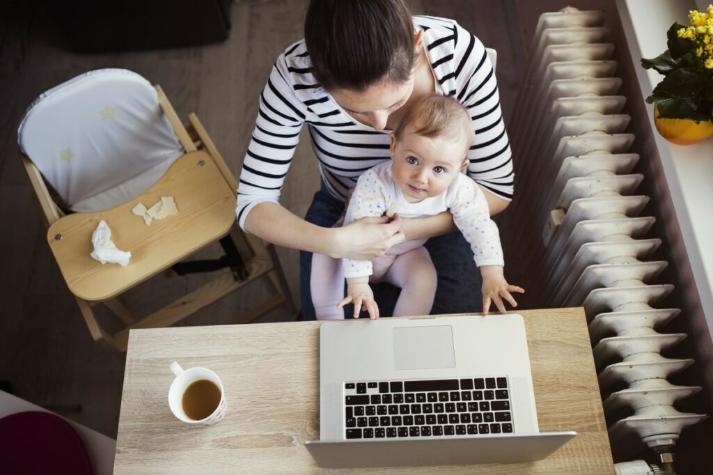 top view of woman sitting at a desk, a laptop and a cup of tea on the desk, a baby on her lap