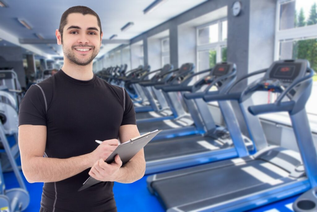 man in a tight black shirt standing in a gym in front of a bunch of treadmills, holding a clipboard and pen, smiling