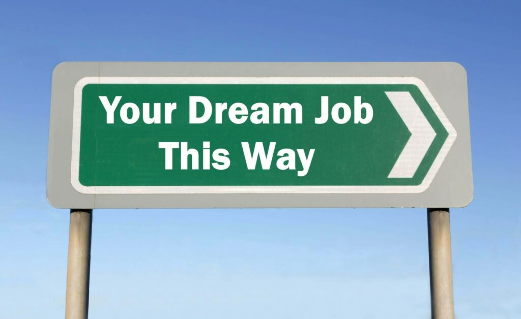 Green sign with white letters spelling Your Dream Job This Way