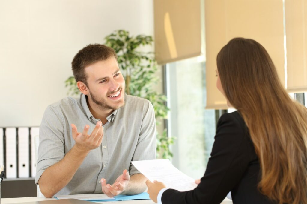 Two people sitting at the table during a job interview, one holding a resume, the other one talking confidently and showing confidence with his body language