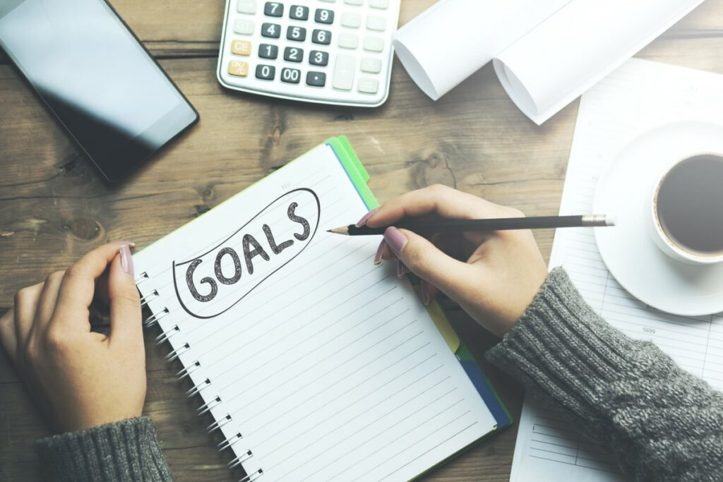 Hands of a woman noting down her goals at job search on a ruled notebook with the word goals in black capital letters