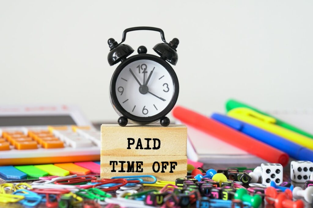 black alarm clock on a wooden cube saying PAID TIME OFF and colorful office supplies like paperclips and pens lying around