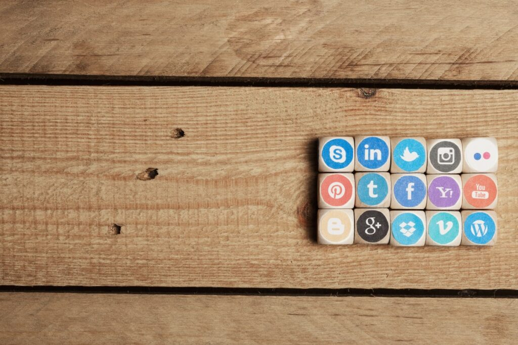 dice with printed on social media icons on a wooden table