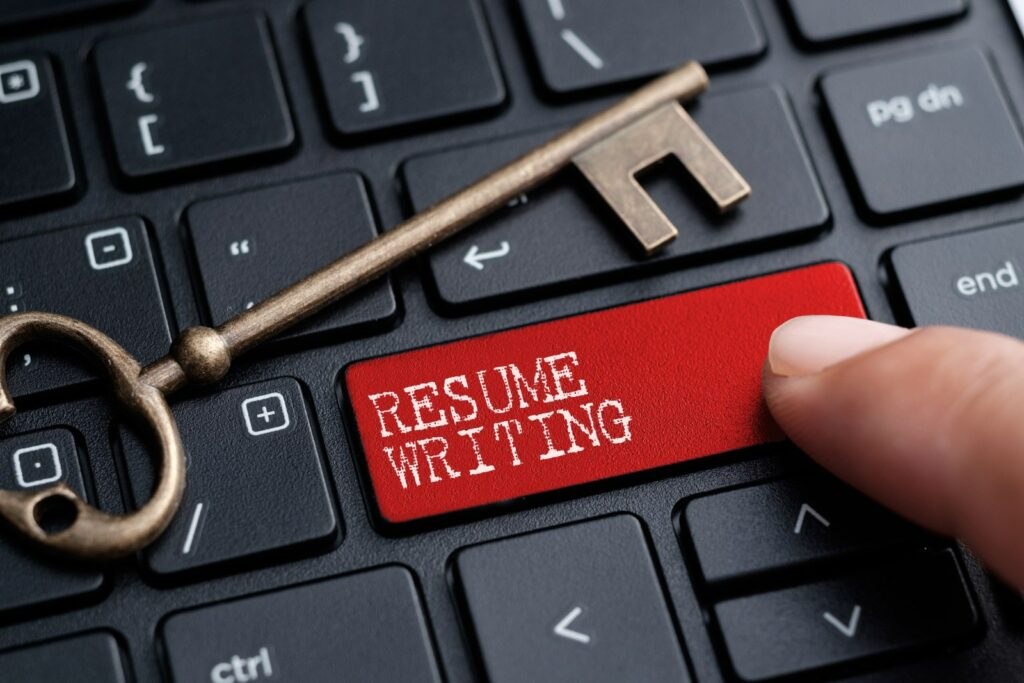 """A key is laying a a keyword while a finger is pressing the """"resume writing"""" button"""