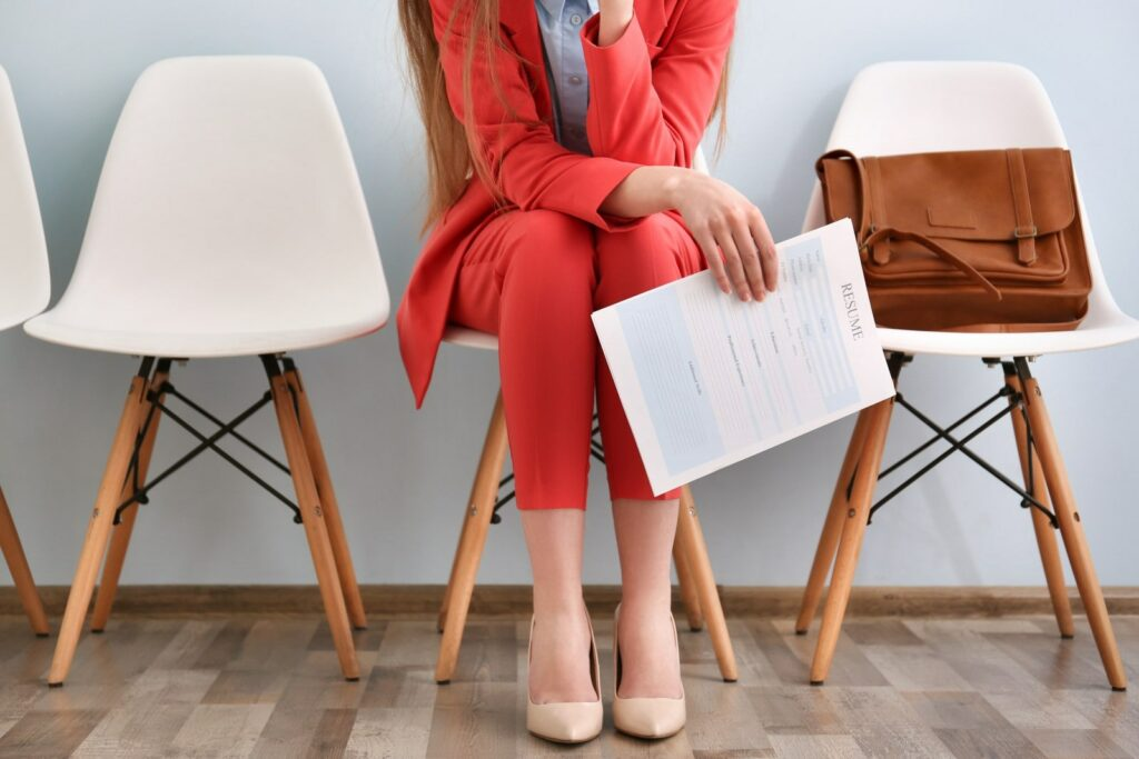 A woman that is dressed in red, sitting on a chari holding her resume in her right hand