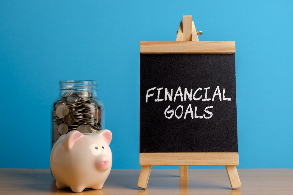 tiny blackboard with financial goals written on it with white chalk, piggy bank and jar with coins standing next to it
