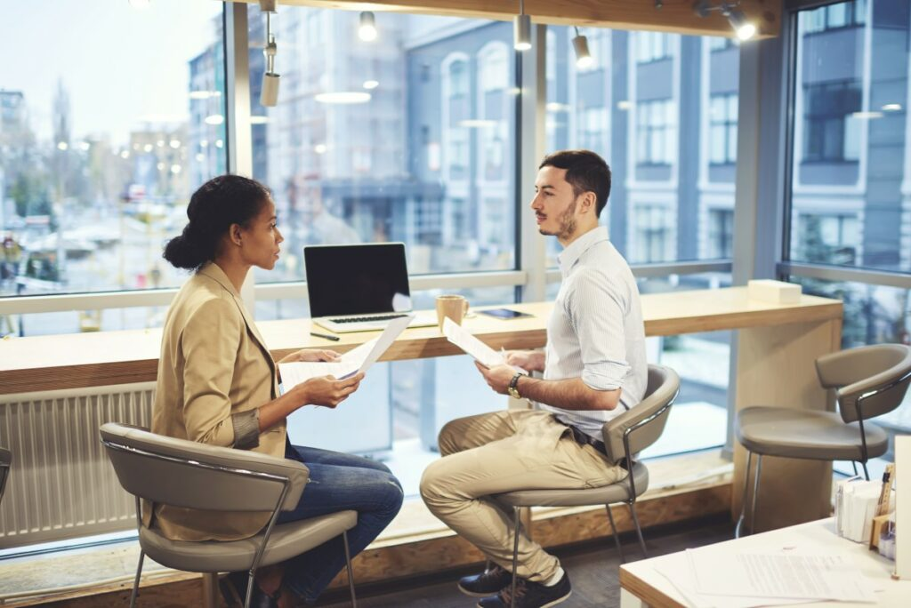 Two people sitting in chairs, wearing business clothes and holding paper in their hands