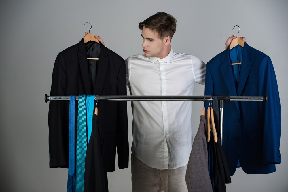 A man thinks about which outfit to choose for his online job interview