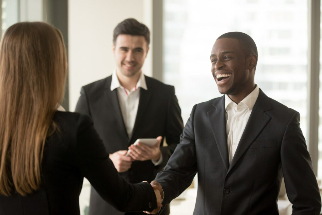 two person shaking hands after a perfect job interview. A third person standing in the background is smiling aswell.