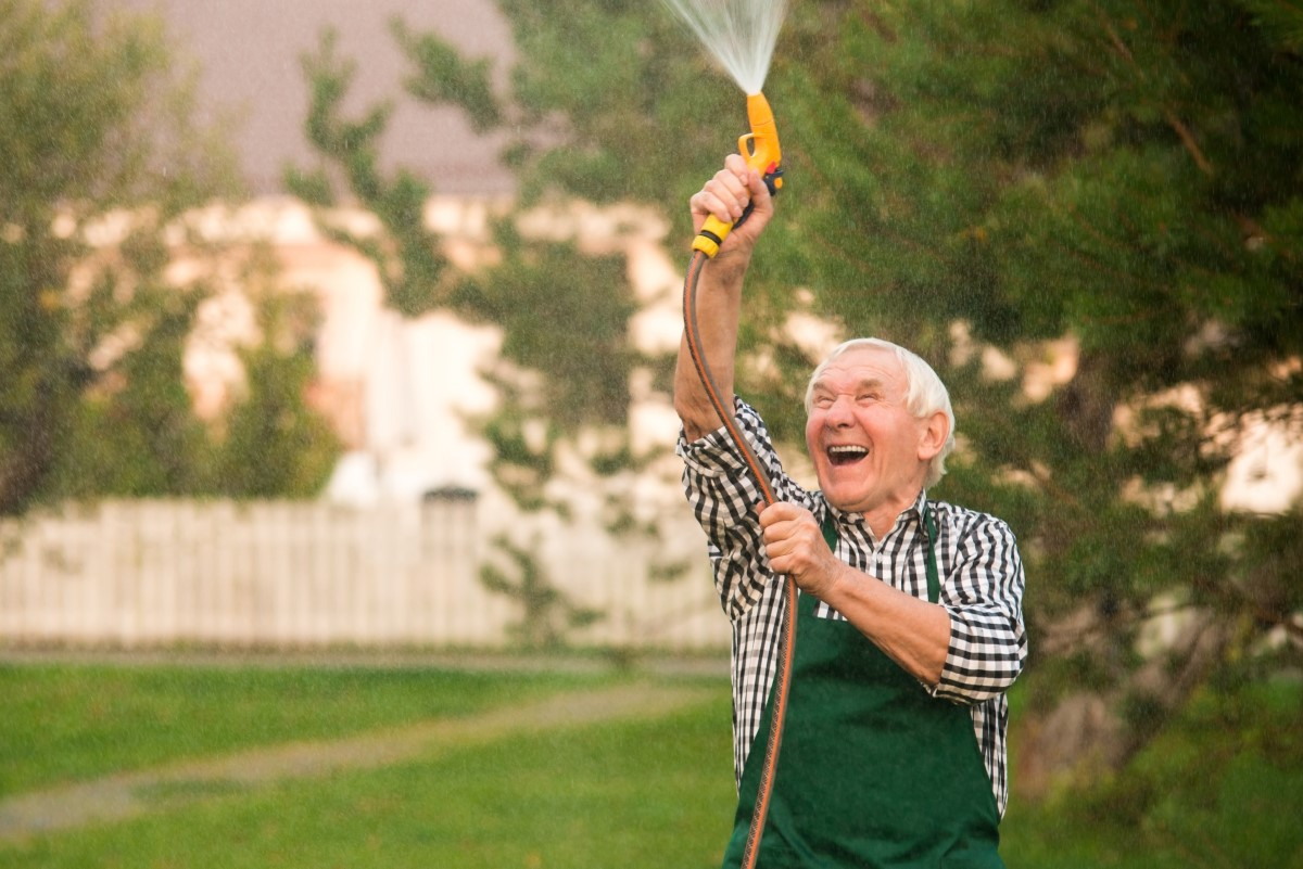 elderly man wearing a plaid shirt and green overalls spraying water up in the air with a garden hose, laughing