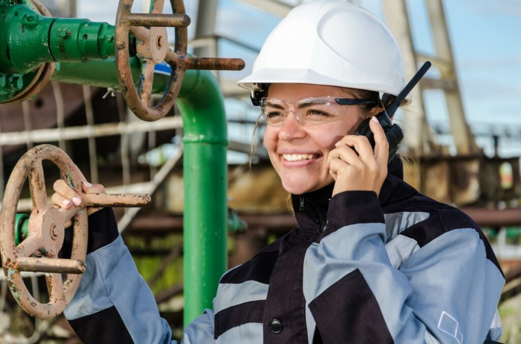 Female engineer with a white construction helmet and safety goggles smiling and talking on a cell phone holding the vent of a pipe system