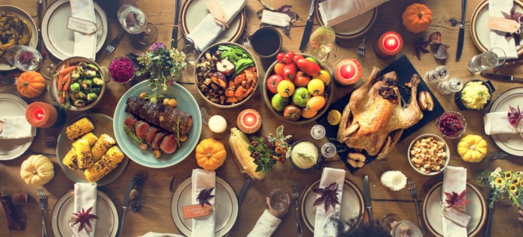 well-laid thanksgiving dinner table with stuffed turkey, fruit, vegetables, beef, corn, and more