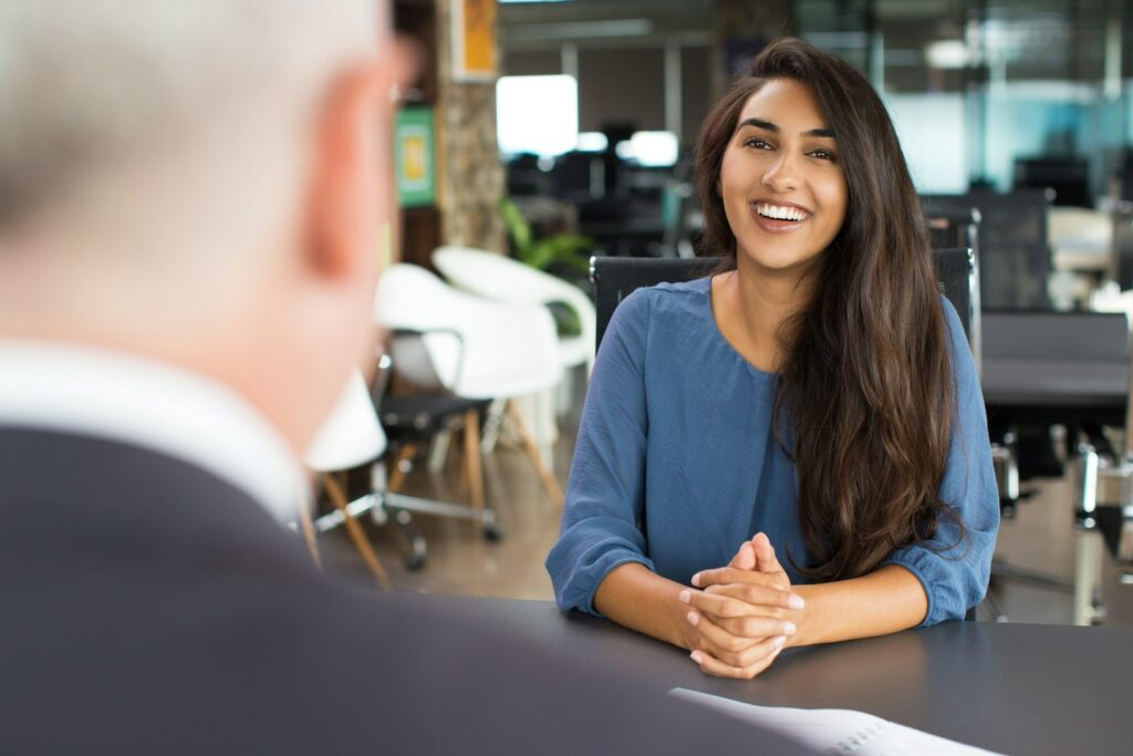 Woman sitting in front of a man smiling in the job interview