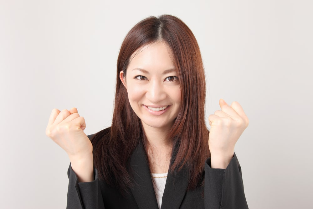 Woman with jacket clenches her fists and rejoices